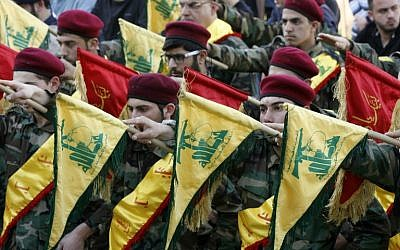 Members of Lebanon's Shiite Hezbollah hold their flags during the funeral of a Hezbollah fighter, who was killed while fighting alongside Syrian government forces in Syria, March 1, 2016. (AFP/Mahmoud Zayyat)