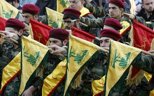 Members of Lebanon's Shiite movement Hezbollah hold their flags during the funeral of a Hezbollah fighter, who was killed while fighting alongside Syrian government forces in Syria, March 1, 2016. (AFP/MAHMOUD ZAYYAT)