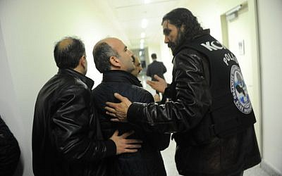 Turkish police officers escort Abdulhamit Bilici (C), editor in chief of Zaman, out of the newspaper's Istanbul headquarters on March 5, 2016. (AFP/SELAHATTIN SEVI)