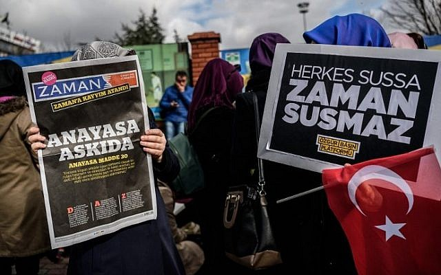 A Zaman supporter reads the latest edition of the Turkish daily newspaper in front of the newspaper's headquarters in Istanbul on March 5, 2016, after Turkish authorities seized the headquarters in a midnight raid. (AFP/Ozan Kose)