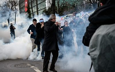 Men run and cover their faces as Turkish anti-riot police officers use tear gas to disperse supporters in front of the headquarters of the Turkish daily newspaper Zaman in Istanbul on March 5, 2016, after Turkish authorities seized the headquarters in a midnight raid. (AFP/OZAN KOSE)