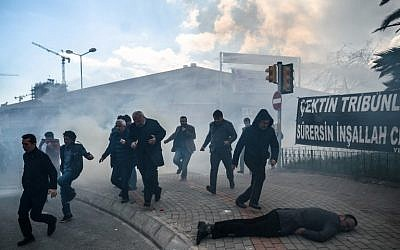 A man lies on the ground as others run as Turkish anti-riot police officers use tear gas to disperse supporters in front of the headquarters of the Turkish daily newspaper Zaman in Istanbul on March 5, 2016, after Turkish authorities seized the headquarters in a midnight raid. (AFP / OZAN KOSE)