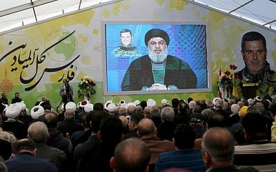 Supporters of Lebanon's Shiite Hezbollah group watch a televised speech by leader Hassan Nasrallah in the southern town of Insar, Lebanon, March 6, 2016. (AFP/Mahmoud Zayyat)