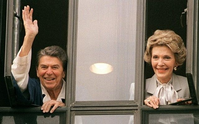 The then US President Ronald Reagan waving to the press from the window of his room at Bethesda Naval Hospital with First Lady Nancy Reagan, January 06, 1987. (AFP/MIKE SARGENT)
