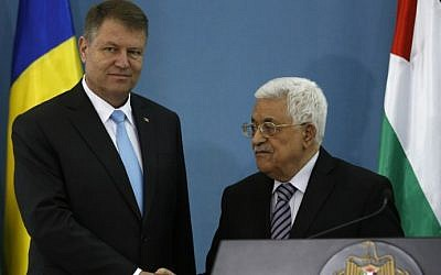 Palestinian Authority President Mahmoud Abbas (R) and Romanian President Klaus Iohannis shake hands during a joint press conference in the West Bank city of Ramallah on March 10, 2016. (AFP/ABBAS MOMANI)