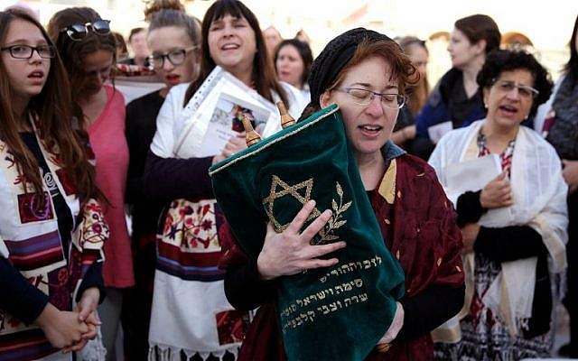 A member of the Women of the Wall wears a tallit (prayer shawl)  as she prays holding a Torah scroll at the Western Wall in Jerusalem on March 11, 2016 (AFP/GALI TIBBON)