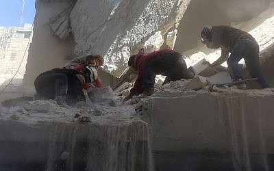 Syrian rescue workers and residents try to pull a man out from under the rubble of a building following a reported air strike on the rebel-held neighborhood of Salhin in the northern city of Aleppo on March 11, 2016. (AFP/THAER MOHAMMED)