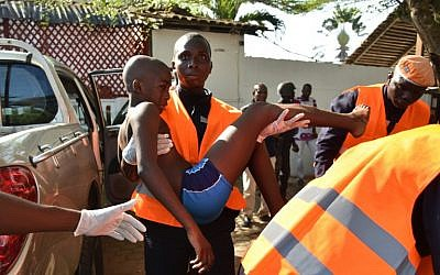 An emergency worker carries a young boy who was injured during an attack on the beach at the hotel Etoile du Sud in Grand Bassam, Ivory Coast, March 13, 2016. (AFP/Sia KAMBOU)