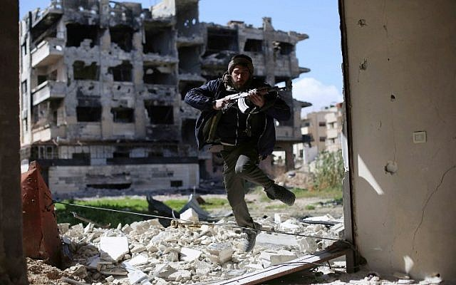 A fighter belonging to Jaish al-Islam (Islam Army) runs to take cover near the frontline on March 14, 2016 in the neighbourhood of Jobar, on the eastern outskirts of the capital Damascus. (AFP / AMER ALMOHIBANY)