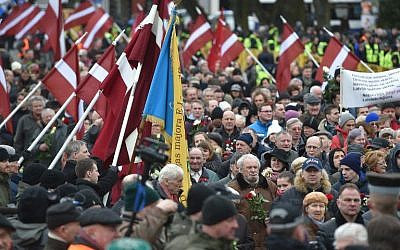 Veterans of the Latvian Legion, a force that was commanded by the German Nazi Waffen SS during WWII, and their sympathizers carry flowers as they walk to the Monument of Freedom in Riga, Latvia, March 16, 2016. (AFP/Ilmars Znotins)