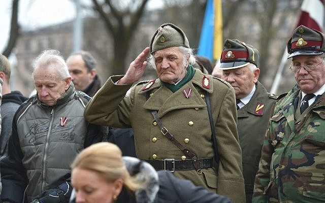A man dressed in a pre-WWII Latvian military uniform salutes as veterans of the Latvian Legion, a force that was commanded by the German Nazi Waffen SS during WWII, and their sympathizers walk to the Monument of Freedom in Riga, Latvia, March 16 (AFP/Ilmars Znotins)