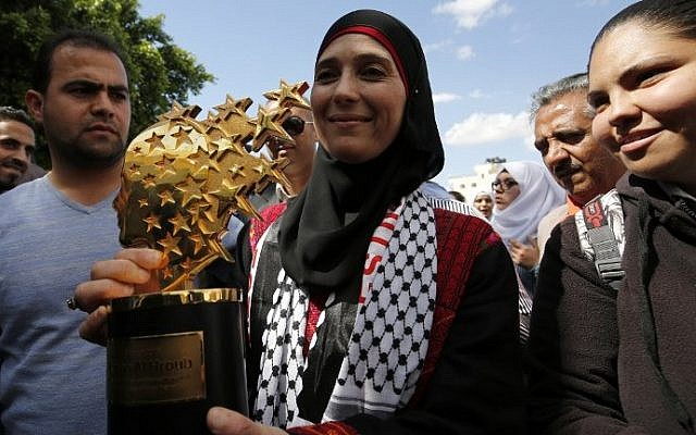 Hanan al-Hroub, a Palestinian teacher who won the $1 million Global Teacher award poses with her trophy during a public reception in the West Bank city of Jericho on March 16, 2016. (AFP/ABBAS MOMANI)