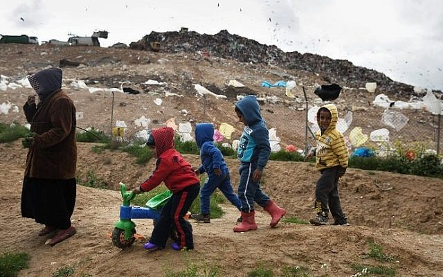 File: This file photo taken on February 7, 2016 shows Israeli Arab Bedouin children of the Tarabin tribe playing in their unrecognized Bedouin village next to the Dudaim dump site (background), the biggest landfill in Israel near the city of Rahat in southern Israel. (Menahem Kahana/AFP)
