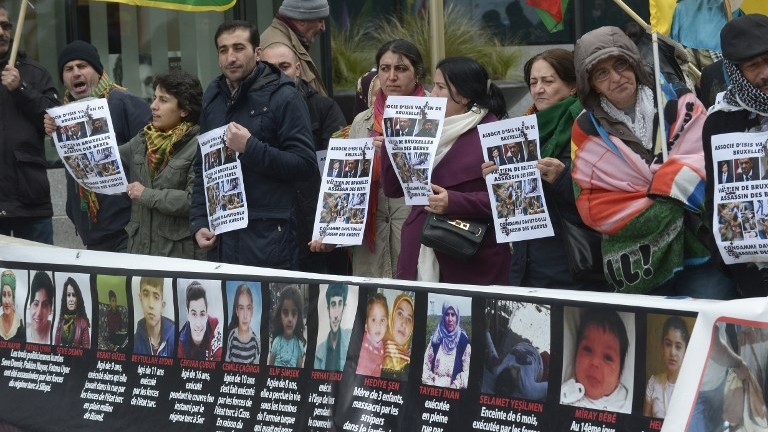 """Kurdish people hold placards depicting Turkish leaders and reading """"partner of the Islamic State group (IS)"""" as they take part in a protest to call for an end of the Turkish State terror in Kurdistan, during the European Union summit in Brussels on March 18, 2016. (John Thys/AFP)"""