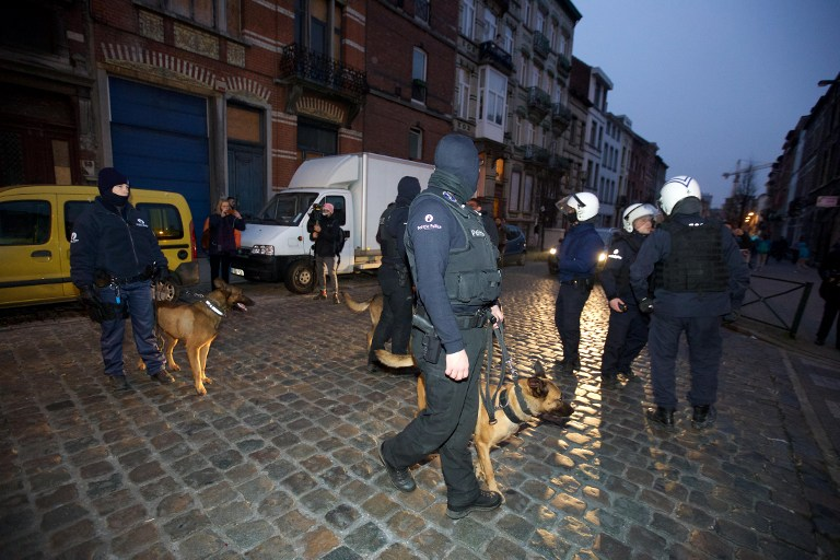 Police dog handlers stand guard the streets at Rue de la Carpe in Molenbeek-Saint-Jean in Brussels, on March 19, 2016, early morning. (AFP/Belga/Nicolas Maeterlinck)