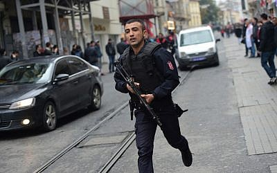 A Turkish policeman runs after an explosion on the pedestrian Istiklal avenue in Istanbul on March 19, 2016. (AFP / Bulent KILIC)