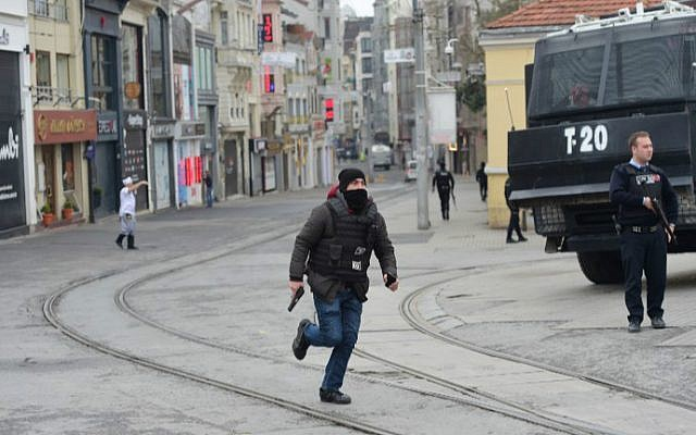 A Turkish policeman runs on the pedestrian Istiklal avenue in Istanbul on March 19, 2016, after four people were killed and some 36 injured in a suicide attack at the site. (Bulent Kilic/AFP)