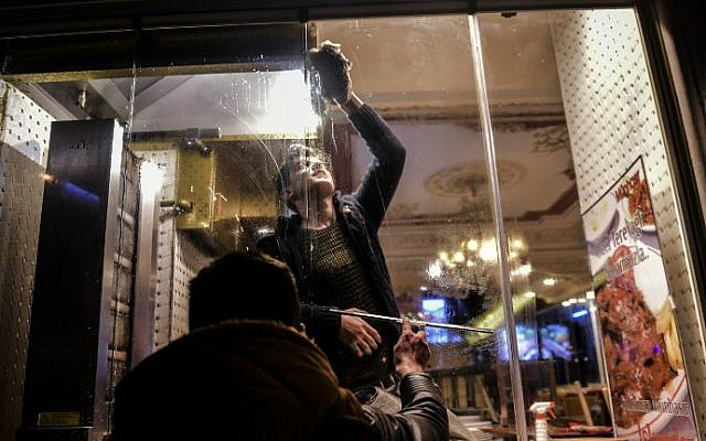 Two men clean the windows of a restaurant near the site of a suicide bombing on Istiklal Street, a major shopping and tourist district in central Istanbul on March 19, 2016. (Bulent Kilic/AFP)