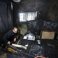 A Palestinian police member inspects the damage inside a burned-out house belonging to a key witness to an arson attack last year by Jewish extremists that killed a Palestinian family, in the West Bank village of Duma, after fire broke out in the home in the early hours of March 20, 2016. (AFP/Jaafar Ashtiyeh)
