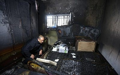 Illustrative: A Palestinian police member inspects the damage inside a burned-out house belonging to a key witness to an arson attack last year by Jewish extremists that killed a Palestinian family, in the West Bank village of Duma, after fire broke out in the home in the early hours of March 20, 2016. (AFP/Jaafar Ashtiyeh)