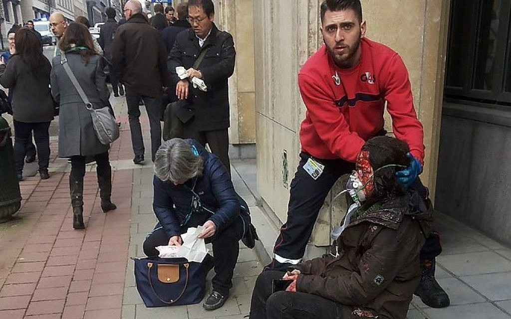 A private security guard helps a wounded women outside the Maalbeek metro station in Brussels on March 22, 2016 after a blast at this station located near the EU institutions. (AFP / Michael VILLA)