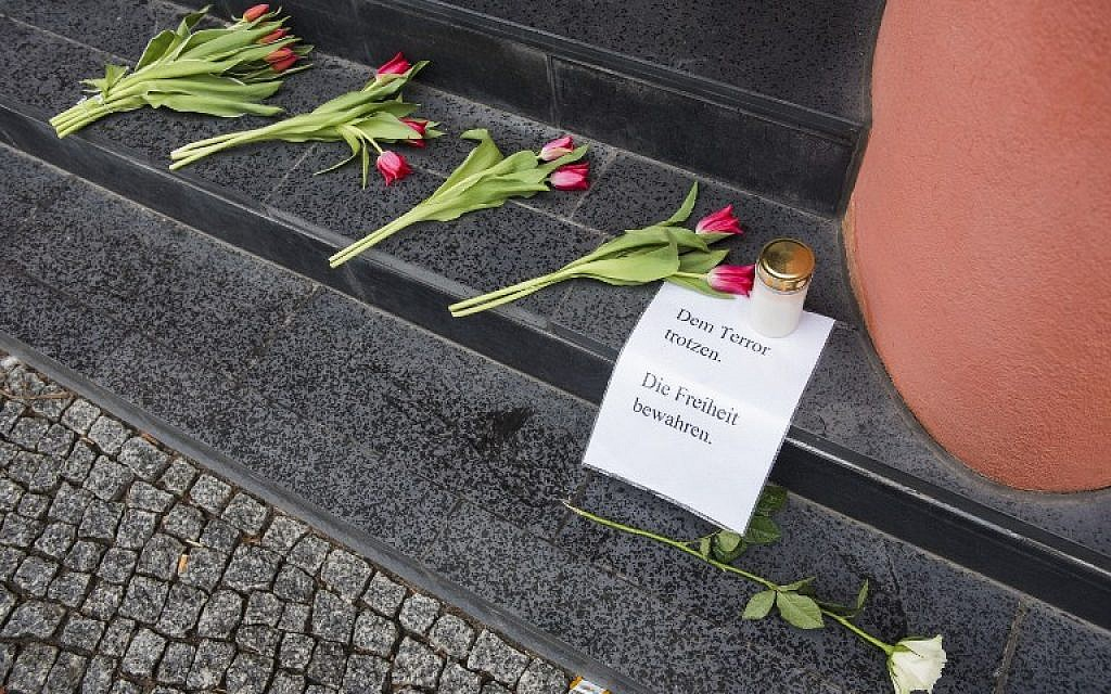 "A man looks at flowers and a sign reading ""Defy terror, protect freedom"" outside the Belgium Embassy in Berlin on March 22, 2016 (AFP / ODD ANDERSEN)"