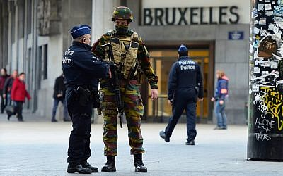 A Belgian soldier speaks to a police officer outside Brussels Central Station as people are allowed in small groups of ten to reach the station in order to take their commuter train following attacks in Brussels on March 22, 2016. (AFP / EMMANUEL DUNAND)