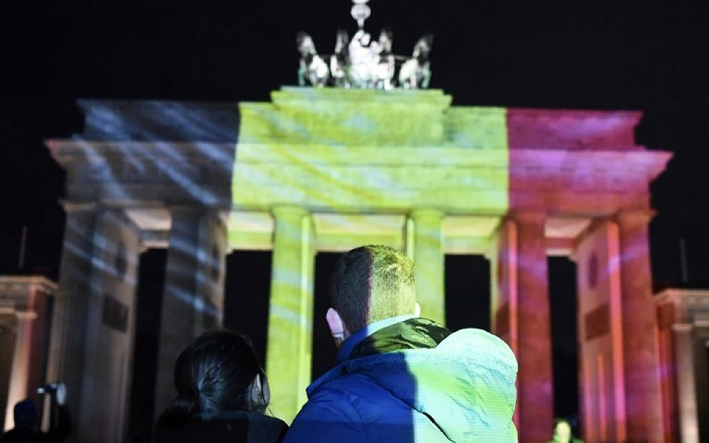 A couple watches as the colors of the Belgian flag are projected on to the Brandenburg Gate in Berlin as the German capital shows its solidarity following the Brussels attacks on March 22, 2016. (AFP / ODD ANDERSEN)