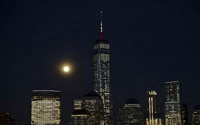 The full moon rises behind One World Trade Center on March 22, 2016, in New York, its mast displaying the colors of the Belgian flag in a show of support following the terrorist attacks in Brussels. (AFP/Trevor Collens)