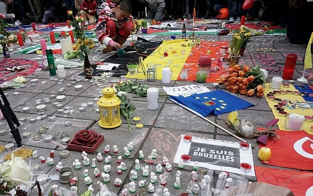 People gather to observe a minute of silence in memory of the victims of the Brussels airport and metro bombings a day earlier, on the Place de la Bourse in central Brussels, March 23, 2016 (AFP/Patrik Stollarz)