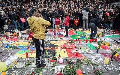 People gather to observe a minute of silence in memory of the victims of the Brussels airport and metro bombings, on the Place de la Bourse in central Brussels, on March 23, 2016, a day after the triple blasts killed some 30 people and left around 250 injured. (AFP/Belga/AURORE BELOT)