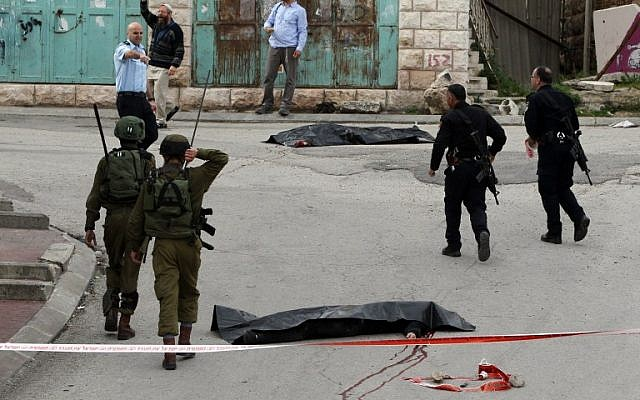 Israeli soldiers and police surround the bodies of two Palestinians who had wounded an Israeli soldier in a knife attack in the West Bank city of Hebron, March 24, 2016. (AFP/Hazem Bader)