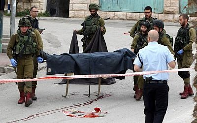 Israeli soldiers carry the body of one of the two Palestinians who were killed after wounding an Israeli soldier in a knife attack before being shot dead by troops at the entrance to the Jewish enclave of Tal Rumeida in the city center of the West Bank town of Hebron, March 24, 2016. (AFP/Hazem Bader)