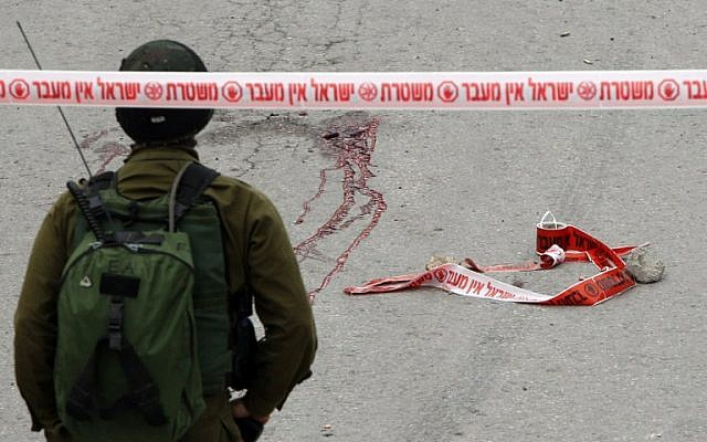 An IDF soldier stands near blood stains from the body of a Palestinian assailant allegedly shot in the head by a soldier as he lay wounded on the ground after stabbing and injuring an Israeli soldier in Hebron on March 24, 2016. (AFP/Hazem Bader)