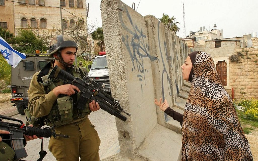 A Palestinian woman speaks with an Israeli soldier at the scene of an attack in which two Palestinians wounded an Israeli soldier in a knife attack before being shot dead by troops in the city center of the West Bank town of Hebron on March 24, 2016. (AFP/Hazem Bader)