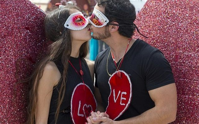A dressed up Israeli couple kisses during a parade as part of the festivities of the Jewish feast of Purim on March 24, 2016 in the central Israeli city of Netanya. The carnival-like Purim holiday is celebrated with parades and costume parties to commemorate the deliverance of the Jewish people from a plot to exterminate them in the ancient Persian empire 2,500 years ago, as recorded in the Biblical Book of Esther. / AFP / JACK GUEZ