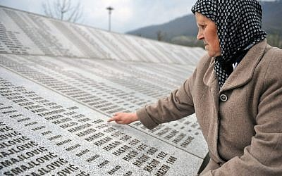 Bida Smajlovic, 64, survivor of July 1995 massacre in Srebrenica, stands at a memorial center in Potocari, on March 24, 2016, while pointing at the name of her husband, engraved among names of other victims of the massacre. (AFP / ELVIS BARUKCIC)