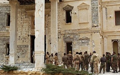 Syrian troops stand next to a mansion belonging to the Qatari royal family in the ancient city of Palmyra on March 24, 2016. (AFP/STR)