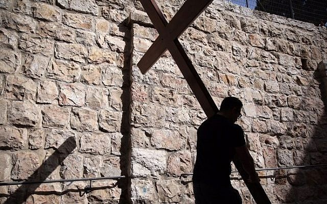A Catholic pilgrim carries a wooden cross along the Via Dolorosa (Way of Suffering) in Jerusalem's Old City during the Good Friday procession on March 25, 2016. (Gali Tibbon/AFP)