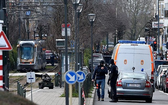 Belgian police stand by as a bomb squad robot moves toward a suspicious object at a tramway station on March 25, 2016 in Schaerbeek suburb of Brussels, during the arrest of a suspect in a fresh anti-terrorist operation. (AFP/PATRIK STOLLARZ)