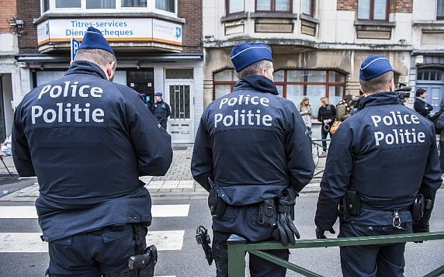 Three police officers stand guard at the Meiser neighborhood in Schaarbeek on March 25, 2016 during an anti-terrorist operation searching for suspects of March 22 terrorist attacks in Brussels. (AFP/Belga/Laurie Dieffembacq)