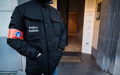 A police officer stands guard at the entrance of a building in Avenue des Cerisiers -  Kerselarenlaan in Schaerbeek - Schaarbeek district in Brussels on March 25, 2016 where the Belgian police had a part of an anti-terrorist operation linked to Brussels attacks of March 22.  (AFP / BELGA / Aurore Belot)