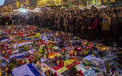 A picture taken on March 25, 2016 shows people gathering at a makeshift memorial in tribute to the victims of the Brussels terror attacks, on Place de la Bourse square in Brussels. (LAURIE DIEFFEMBACQ / Belga / AFP)