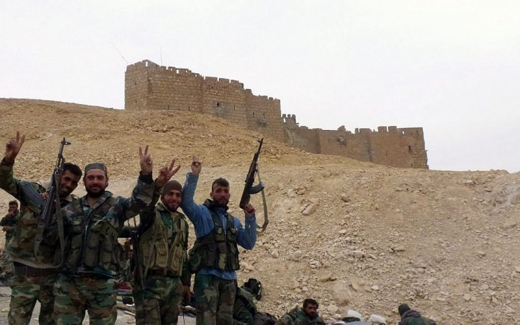Syrian pro-government forces gesture next to the Palmyra citadel on March 26, 2016, during a military operation to retake the ancient city from the Islamic State group (AFP / Maher AL MOUNES)