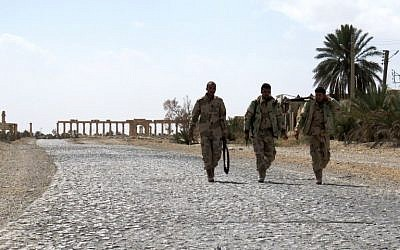 Syrian troops walk in the ancient city of Palmyra after they recaptured the site from the Islamic State group on March 27, 2016. (AFP/Stringer)