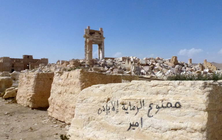 """A general view shows graffiti on a stone reading in Arabic: """"Shooting without the permission of the chief is prohibited"""" near the remains of the entrance to the iconic Temple of Bel that was destroyed by Islamic State (IS) group jihadists in September 2015 in the ancient city of Palmyra, after government troops recaptured the UNESCO world heritage site from IS jihadists on March 27, 2016. / AFP / Maher AL MOUNES / """""""