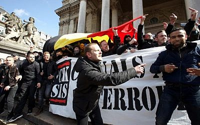 Far-right football hooligans chant slogans as they hold a banner of the 'FCK-Casuals' hooligan movement, as they arrive in the square outside the stock exchange in Brussels on March 27, 2016 an area which has become an unofficial shrine to victims of the March 22 terror attacks. (AFP/Belga/NICOLAS MAETERLINCK)