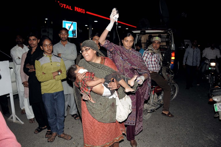 Pakistani relatives bring an injured child to the hospital in Lahore on March 27, 2016, after at least 56 people were killed and more than 200 injured when an apparent suicide bomb ripped through the parking lot of a crowded park in the Pakistani city of Lahore where Christians were celebrating Easter. (AFP/ARIF ALI)