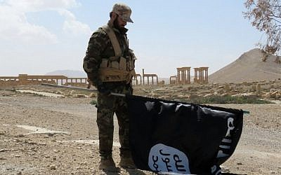 A member of the Syrian pro-government forces carries an Islamic State flag as he stands on a street in the ancient city of Palmyra on March 27, 2016, after troops recaptured the city from IS jihadists. (AFP/STR)