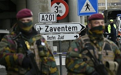 Soldiers stationed in the Belgium capital of Brussels standing in front of a sign to Zaventem airport, March 29, 2016. (AFP/John Thys)